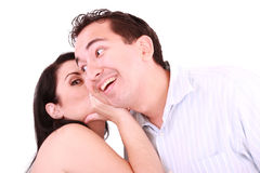 Woman talking secret to young man in his ear Stock Photo