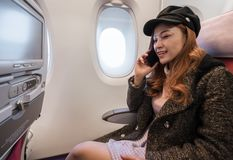 Woman talking with smartphone in airplane in flight time stock photo