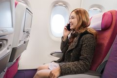 Woman talking with smartphone in airplane in flight time. Woman talking with smartphone in the airplane in flight time royalty free stock photo