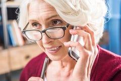 Attractive senior woman in eyeglasses talking royalty free stock image