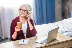 Woman talking on smartphone. Attractive senior woman in eyeglasses talking on smartphone and holding paper cup Stock Image