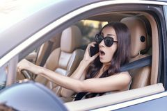 Woman talking on the smartphone while driving a car stock photo