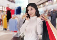 Woman talking on smartphone and holding shopping bags at mall stock photo