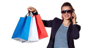 Woman talking on a smartphone and showing shopping bags Royalty Free Stock Photography