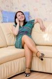 Woman talking on telephone on the sofa Stock Photos
