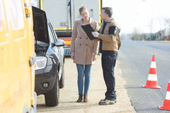 Woman talking to breakdown assistant on roadside Stock Photography