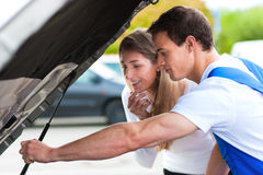 Woman talking to car mechanic in repair shop. Woman talking to a car mechanic in a parking area, both are standing next to the car stock photo