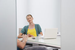 Woman Talking To Cropped Colleague In Office. Beautiful young woman talking to cropped male colleague in office Royalty Free Stock Images