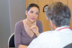 Woman talking to doctor. Woman talking to her doctor royalty free stock images