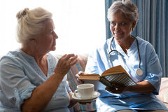 Woman talking to doctor holding book in nursing home. Senior women talking to doctor holding book in nursing home Stock Images