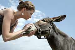 Woman talking to donkey Royalty Free Stock Images