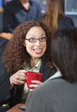 Woman Talking to Friend. Happy business woman with red mug talking to friend Stock Photography