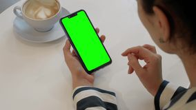 A woman is talking to a friend over a video call on a green-screen smartphone stock video footage