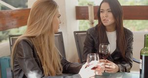Woman talking to friend over wine stock footage