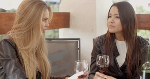 Woman talking to friend over wine stock video footage