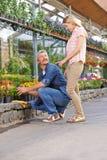 Woman talking to gardener in nursery shop Royalty Free Stock Photos