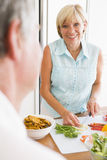 Woman Talking To Husband As She Prepares A meal Stock Photo
