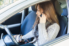 Woman talking to mobile phone and searching purse. Woman sitting in drivers seat of her car , talking to mobile phone and searching purse royalty free stock images