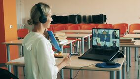 A woman is talking to multiple users during a virtual lesson. Remote education, online college lesson, distant studying