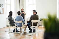 A woman talking to other people during group therapy. stock photography