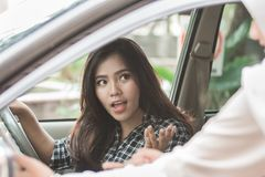 Driver talking to customer. Woman talking to someone while driving a car Royalty Free Stock Photo