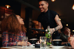 Woman talking to waiter at cafe Stock Photography