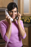 Woman Talking on Two Telephones Royalty Free Stock Photography