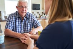 Woman Talking With Unhappy Senior Man Sitting In Kitchen At Home stock images