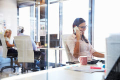 Woman talking using phone at her desk in an office Royalty Free Stock Images