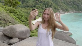 Woman Talking in Video Chat. Young blonde travelling woman using video chat by her smartphone on the mountain with a view over beautiful beach during vacation stock video