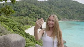 Woman Talking in Video Chat. Young blonde travelling woman using video chat by her smartphone on the mountain with a view over beautiful beach during vacation stock video footage
