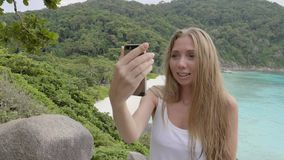 Woman Talking in Video Chat. Young blonde travelling woman using video chat by her smartphone on the mountain with a view over beautiful beach during vacation stock footage