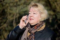 The woman talks on a cellular telephone Stock Photos
