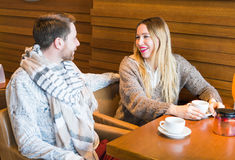 Woman talks with man sitting at the table in coffee house Royalty Free Stock Images