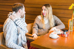 Woman talks with man sitting at the table in coffee house Royalty Free Stock Photography