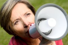 Woman talks through megaphone Stock Photo