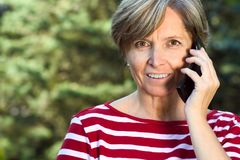 Woman talks on the phone. Middleaged woman talks on the mobile phone royalty free stock photos