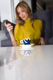 Woman talks on the phone. (focus on the cup of coffee Stock Photography