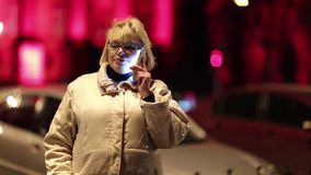 Woman talks on smartphone on the street. Woman with cell phone stands near the road and red building in nighttime. Woman with smartphone speaks and laughs. Woman stock video