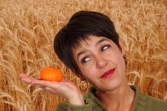 Woman and tangerine. Woman looking at a clementine posed on its hand Royalty Free Stock Image