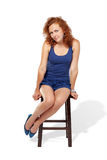 Woman in tank top dress sits on stool Stock Photo