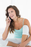 Woman in tank top using mobile phone in bed Stock Photos
