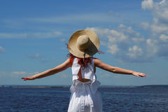 Woman with tanned skin in white dress, back view. Woman with tanned skin in white dress and glamour hat on riverside, back view, deep blue water on background Stock Photos