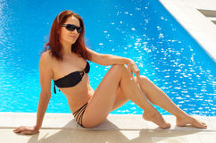 Woman tanning near the sunlit pool Stock Images