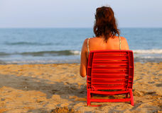 Woman tanning on the seashore at sunset. Young woman tanning on the seashore at sunset Royalty Free Stock Images