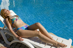 Woman tans. In chaise lounge at pool royalty free stock photography