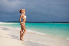 Woman tans standing on the beach looking up Royalty Free Stock Image