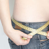 Woman with a tape measure arround her body. Close up of a mid section of a woman wearing jeans with a tape measure around her body Stock Image