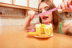 Woman with tape measure and cake. Diet dilemma. Royalty Free Stock Photography
