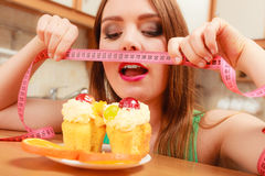 Woman with tape measure and cake. Diet dilemma. Stock Images